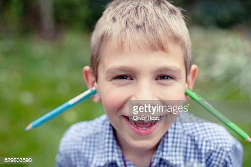 Young boy (8-9) posing with two pens stuck in his ears : Stock Photo