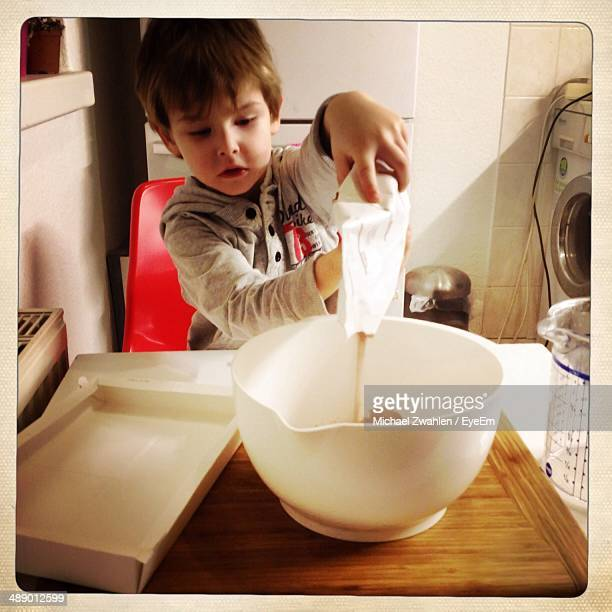 Young boy pouring flour into bowl at home