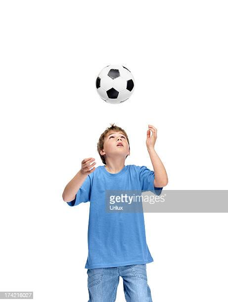 Young boy practcing football on white background