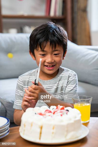 Young boy preparing birthday cake at a family birthday party