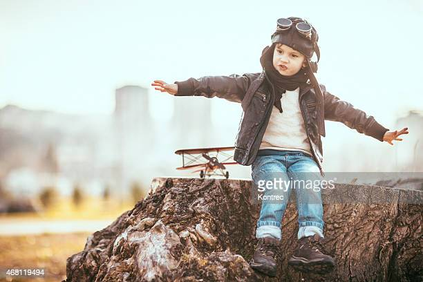 Young boy pretending to fly plane with model plane
