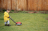 Young Boy Pushing a Toy Lawnmower