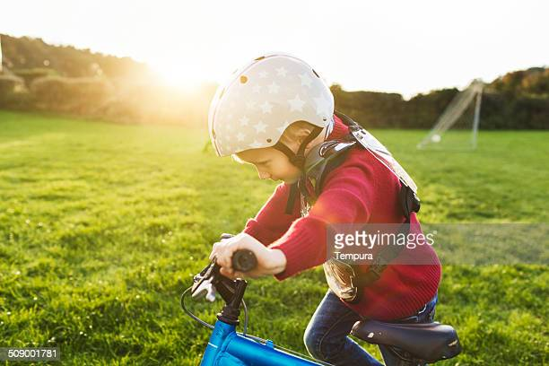 Young boy pushing his bicycle uphill.