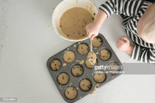 Young boy putting mixture into baking tray, overhead view