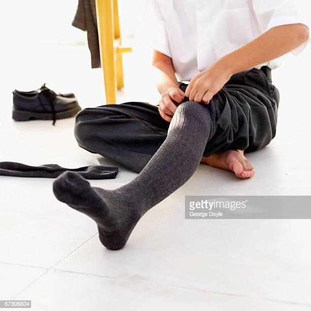 Young boy (10-11) putting on socks