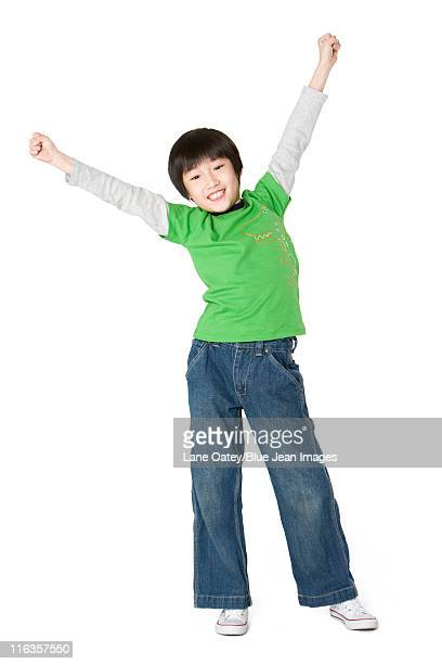 Young boy raising his arms in excitement
