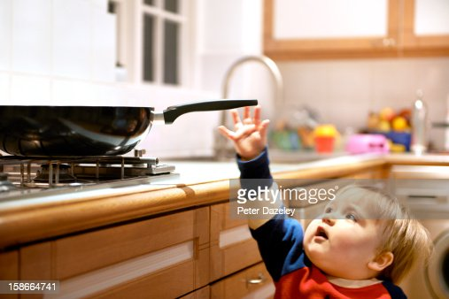 Young boy reaching for a hot pan on a hob : Bildbanksbilder