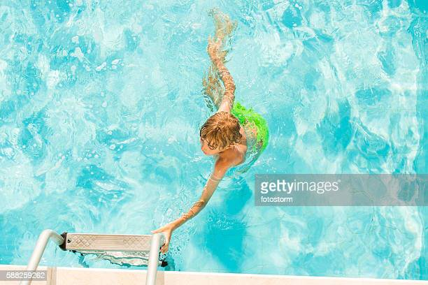 Young boy reaching for pool ladder