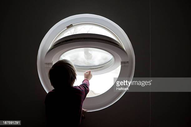 A young boy reaching to open a round window in silhouette