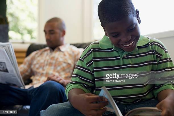Junge liest ein Buch mit Mann sitzt hinter mit Zeitung