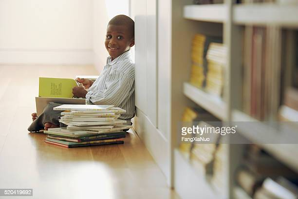 ‡Young boy reading a stack of storybooks