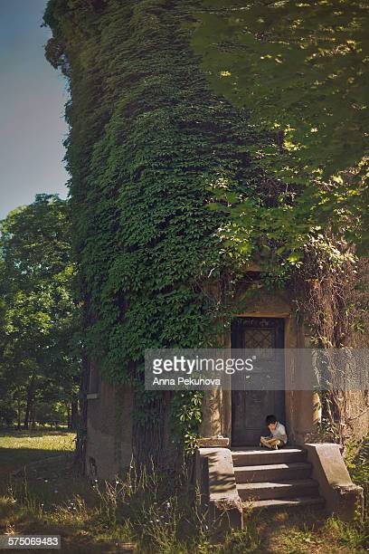 Young boy reading book infront of a tower