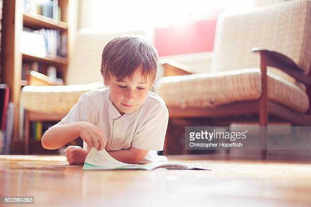 Young boy reading on wooden floor