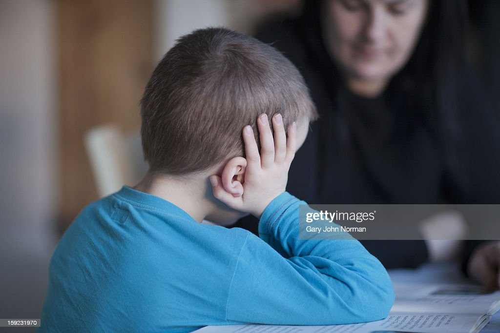 young boy reading to his mother : Stock Photo