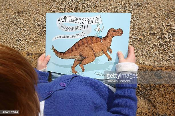 A young boy reads a dinosaur story book which accompanied the launch of a giant interactive dinosaur 'Muttaburrasaurus' on September 8 2014 in...