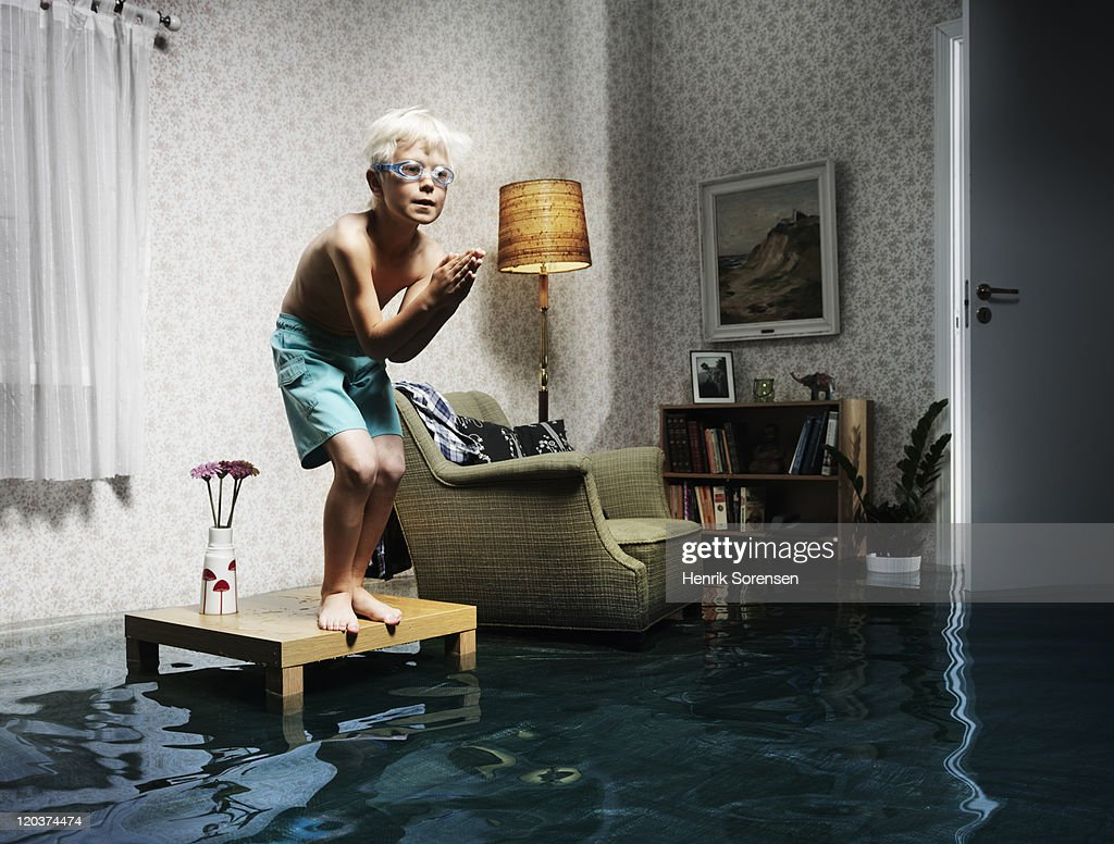 young boy ready to swim in flooded room : Photo