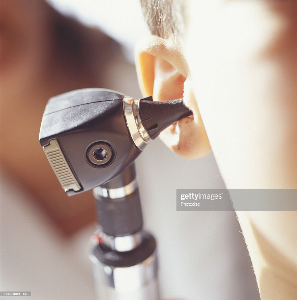 Young boy (6-7) receiving ear check-up, (Close-up) : Stock Photo