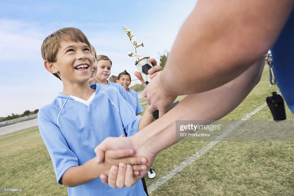 Young boy receiving trophy at sporting event : Stock Photo
