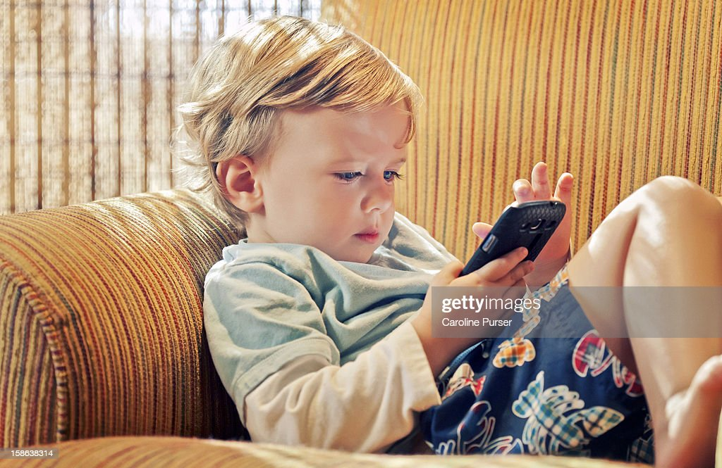 Young boy relaxing, playing on phone : Stock Photo