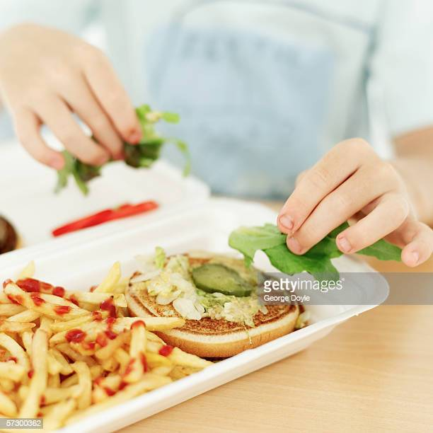 Young boy removing lettuce form a hamburger