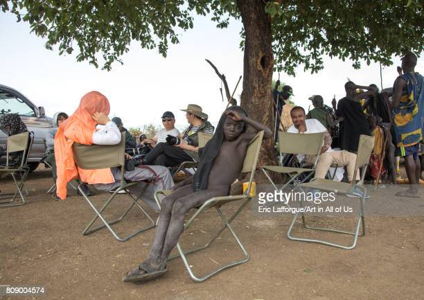 Young boy resting on a camping chair with chinese tourists during the Kael fat men ceremony in the Bodi tribe Omo valley Hana Mursi Ethiopia on June...