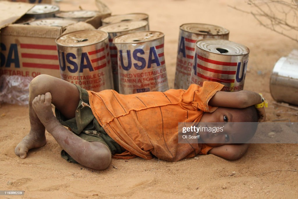 A young boy rests by empty USAID vegetable oil tins in the Dagahaley refugee camp which makes up part of the giant Dadaab refugee settlement on July 19, 2011 in Dadaab, Kenya. The refugee camp at Dadaab, located close to the Kenyan border with Somalia, was originally designed in the early 1990s to accommodate 90,000 people but the UN estimates over 4 times as many reside there. The ongoing civil war in Somalia and the worst drought to affect the Horn of Africa in six decades has resulted in an estimated 12 million people whose lives are threatened.