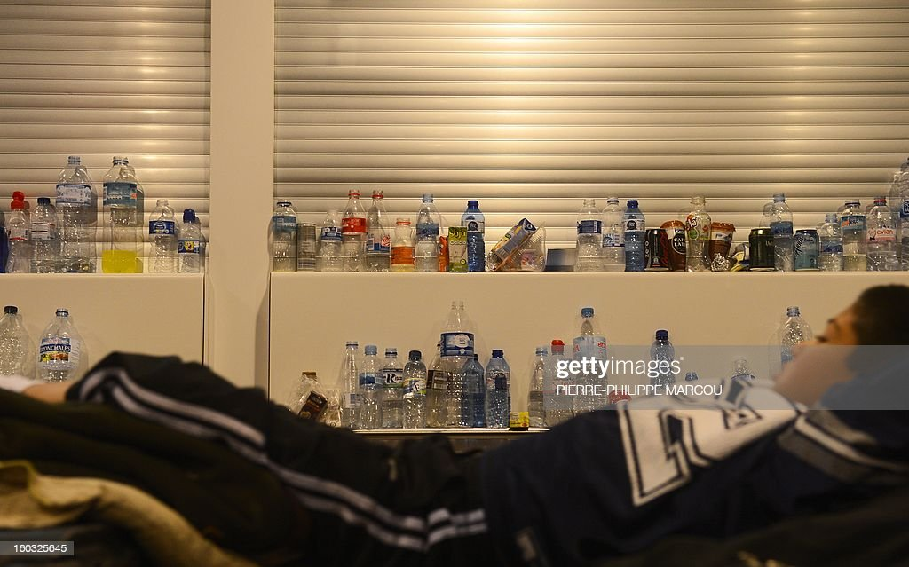 A young boy rests next to uncollected garbage at Barajas airport in Madrid on January 29, 2013. Garbage piled up at Madrid's Barajas airport, one of Europe's busiest, due to a strike by cleaning staff over salary cuts and job losses. MARCOU