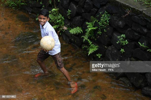 A young boy retrieves his football from a nearby stream during the FIFA U17 World Cup India 2017 tournament at on October 15 2017 in Kochi India