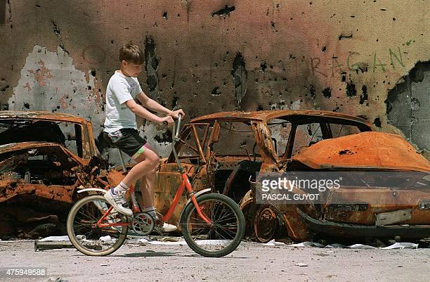 A young boy rides a bicycle 16 july 1992 past the wrecks of several cars destroyed in combat in Sarajevo