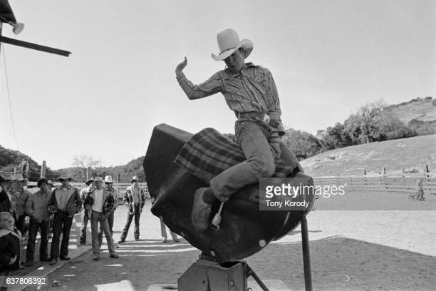 Young boy rides a mechanical bull at a rodeo