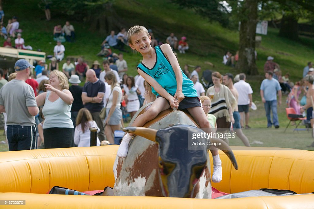 A young boy rides a mechanical bull during the annual Ambleside Sports competition at Rydal Park in the Lake District