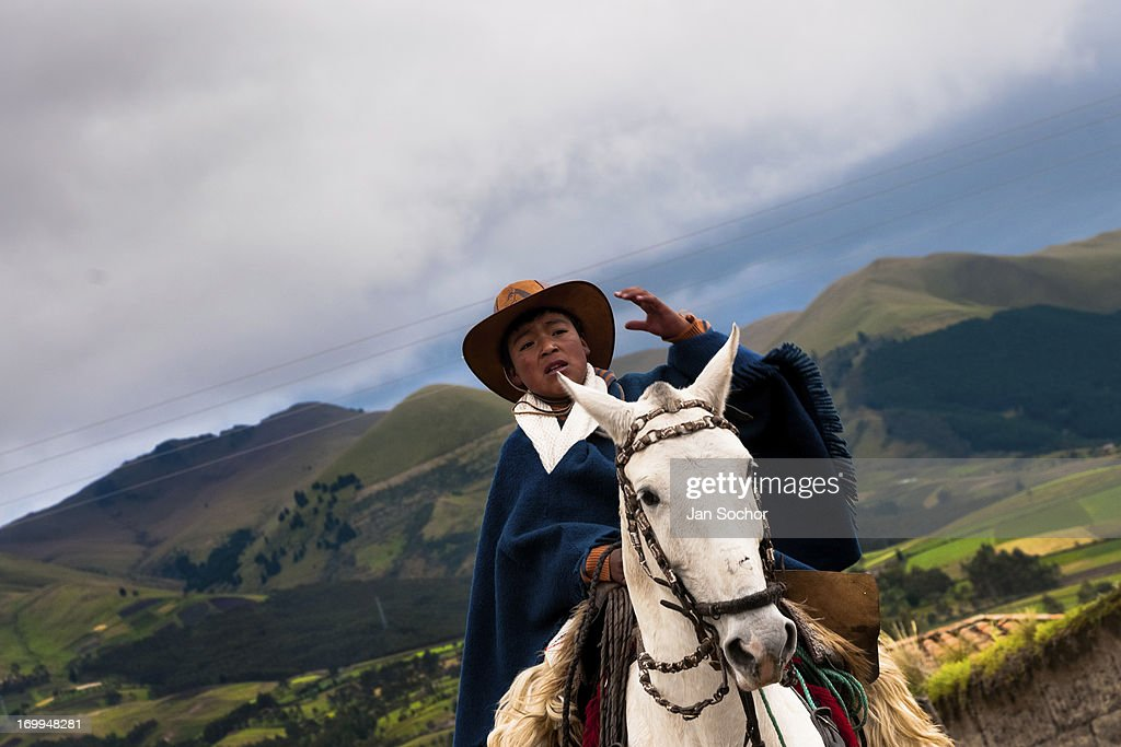 """A young boy rides a white horse during the Inti Raymi festival on 26 June 2010 in the village of Pesillo, Ecuador. Inti Raymi, """"Festival of the Sun"""" in Quechua language, is an ancient spiritual ceremony held in the Indian regions of the Andes, mainly in Ecuador and Peru. The lively celebration, set by the winter solstice, goes on for various days. The highland Indians, wearing beautiful costumes, dance, drink and sing with no rest. Colorful processions in honor of the God Inti (Sun) pass through the mountain villages giving thanks for the harvest and expressing their deep relation to the Mother Earth (Pachamama)."""