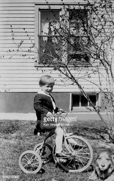 Young boy rides his tricycle with the dog in the backyard