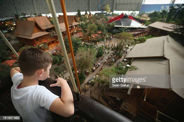 A young boy rides in the basket of a balloon as he looks down at the Thai House and other restaurants located in the Tropical Islands indoor resort...
