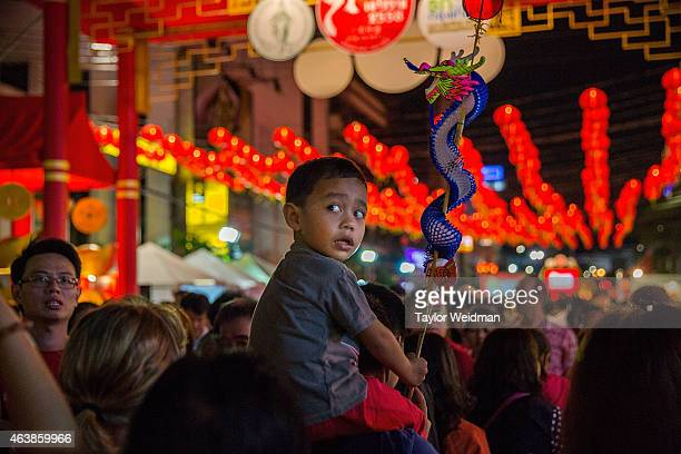 A young boy rides on a man's sholders during Chinese New year on February 19 2015 in Bangkok Thailand February 19 marks the first day of the Chinese...