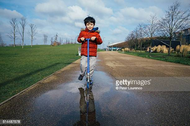 A young boy riding his scooter through a puddle