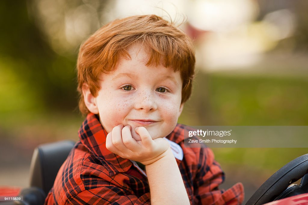 Young boy riding in toy car : Stock Photo