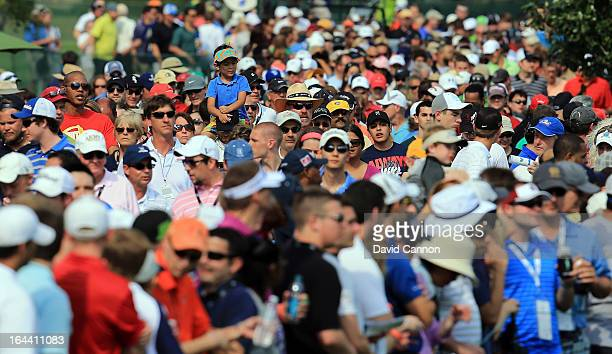 A young boy riding on his father's shoulders amongst the huge gallery following Tiger Woods during the third round of the 2013 Arnold Palmer...