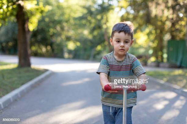 Young boy riding push scooter