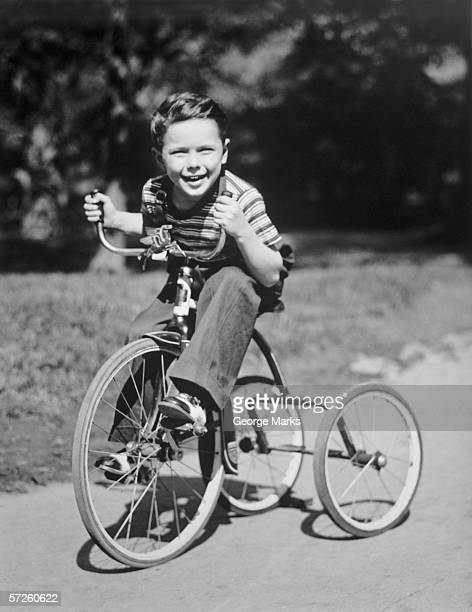 Young boy (6-7) riding tricycle in park, (B&W), portrait