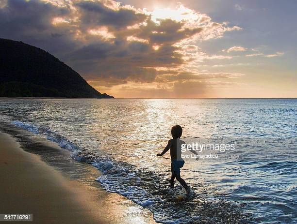Young boy running along the sea