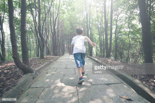 Young boy running in forest