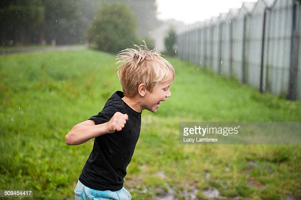 Young boy running in the rain, laughing