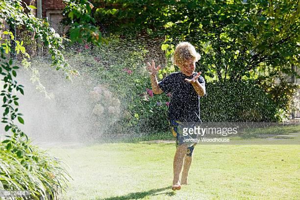 young boy running through sprinkler