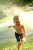 Young boy running through summer sprinkler.
