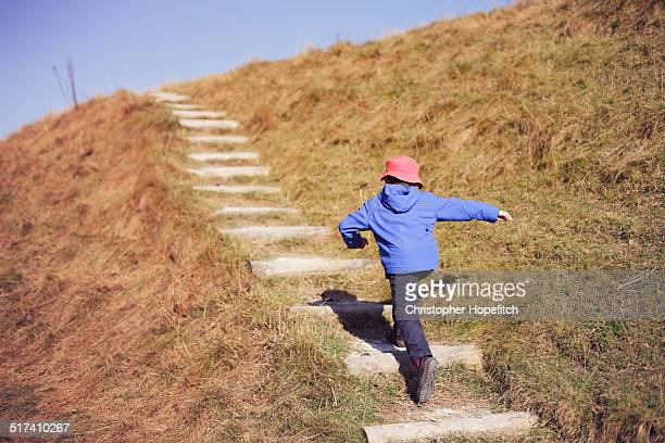 Young boy running up steep path