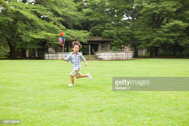 young boy running with pinwheel