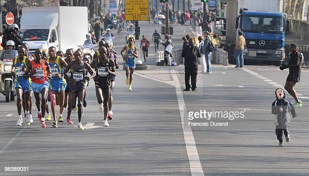 A young boy runs alongside competitors runs during the 34th Paris Marathon on April 11 2010 in Paris France