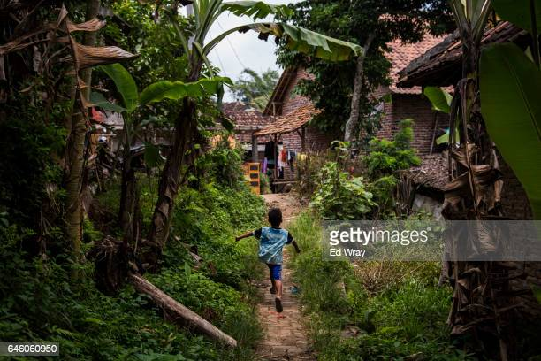 A young boy runs down a footpath in the village where Siti Aisyah the Indonesian women arrested in connection with the assassination of Kim Jongnam...