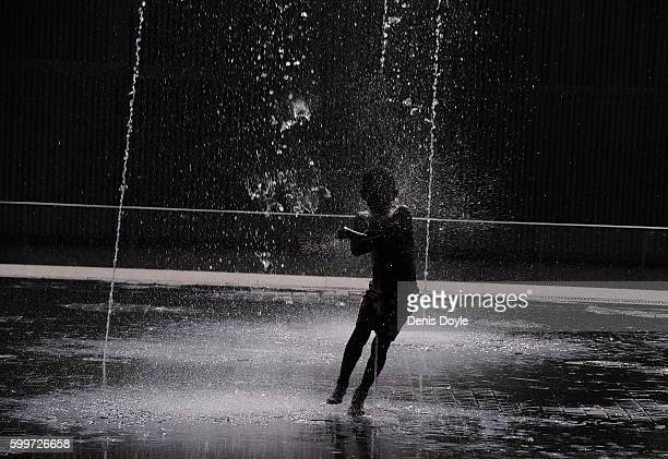 A young boy runs while cooling down in a fountain in the Madrid Rio playground on September 5 2016 in Madrid Spain A threeday heatwave has hit...
